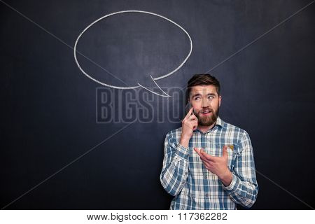 Happy handsome young man with beard talking on mobile phone standing over chalkboard background with blank speech bubble