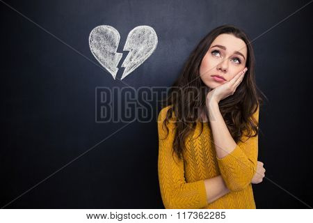 Upset beautiful young woman standing and thinking over background of chalkboard with drawn broken heart