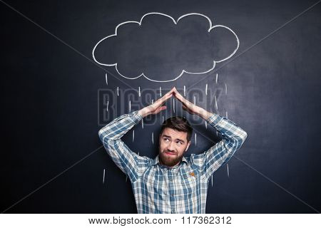 Frowning irritated young man holding hands above head and covering from drawn rain from raincloud over blackboard background
