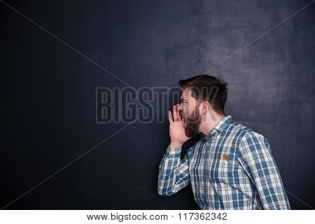 Young man screaming over black background