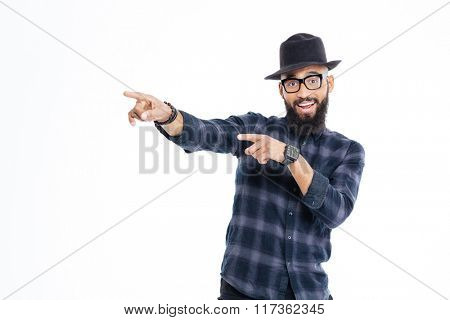 Cheerful young african man with beard in black hat and glasses pointing away with both hands