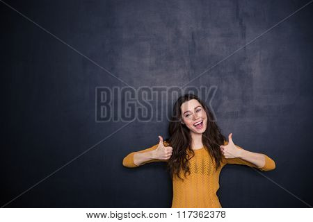 Cheerful woman showing thumbs up over black background