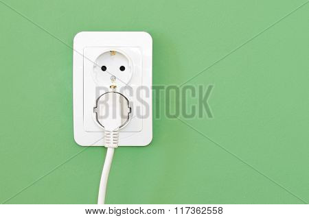 European White Electrical Outlet Socket And White Cable Pluged In On Green Wall