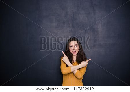 Cheerful young woman pointing fingers away over black background