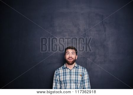 Smiling casual man looking up at copyspace over black background