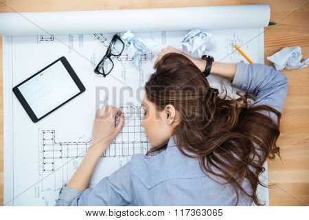Top view of tired young woman lying and sleeping on blueprint