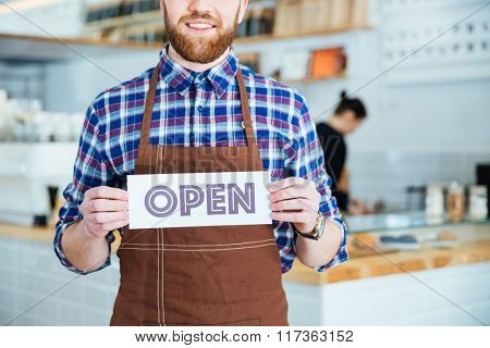 Smiling bearded waiter in brown apron showing open sign at the coffee shop