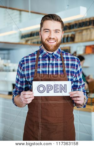 Cheerful handsome cafeteria worker in checkered shirt and brown apron holding sign open in cafe
