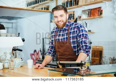Cheerful handsome young barista with beard in brown apron  working in coffee shop