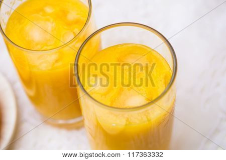 Two Glasses Of Orange Juice With Ice On White