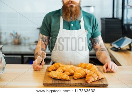 Closeup of bearded man in white apron with tattoo on hands standing in cafe and holding tongs for croissants