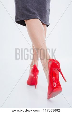 Closeup of slim woman legs running in shoes with high hills over white background
