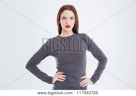 Portrait of attractive gorgeous young woman with red lips in grey dress standing with hands on waist over white background
