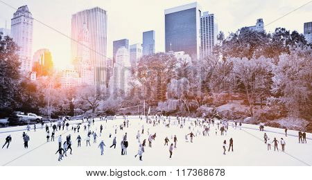 Ice skaters having fun in New York Central Park in fall with sunrise effect