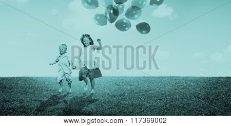 Little Girl and Boy Outdoors Holding Balloons Concept