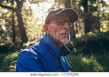 Retired Active Man With Cap In Summer Forest. Backlit.