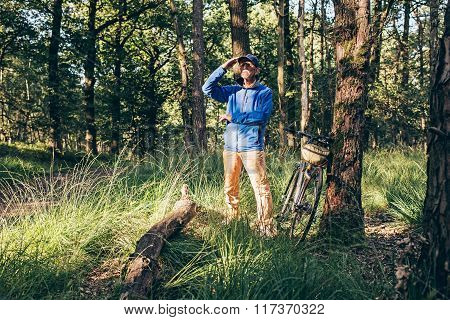 Man Standing In Forest Looking Faraway. Bicycle Standing Against Tree.