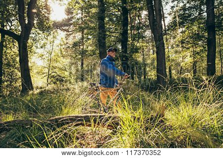 Backlit Retired Man Standing In Forest With Bicycle.