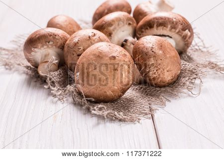 Fresh brown mushrooms on the wooden table.
