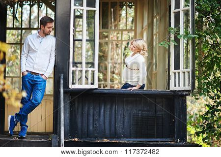 Husband With His Pregnant Wife On The Porch Of The House