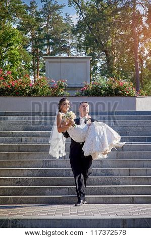 Groom Carries His Bride In His Arms On The Stairs
