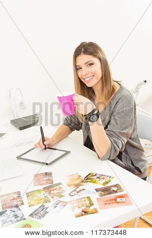 Freelance young female photographer at home office with tablet, pen and coffee