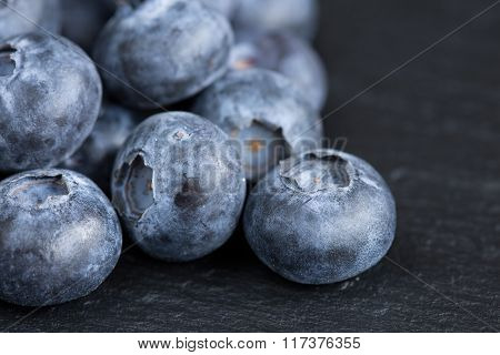 Ripe blueberries on a black slate background