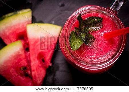 Fresh watermelon smoothie drink in mason jar on black stone.