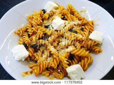 Close-up of fusilli with tomato sauce, parmesan, olives and pieces of cheese