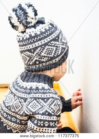 Little Child With Knitted Clothing, Hat And Sweather