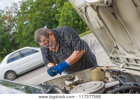 Senior man doing car repair on the road