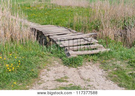 Wooden worn foot-bridge over small stream