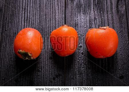 Delicious orange persimmons on wooden table ,healthy food.