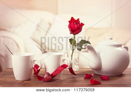 Teacups with red rose in vase for Valentine's Day - toned to give romantic vintage feel