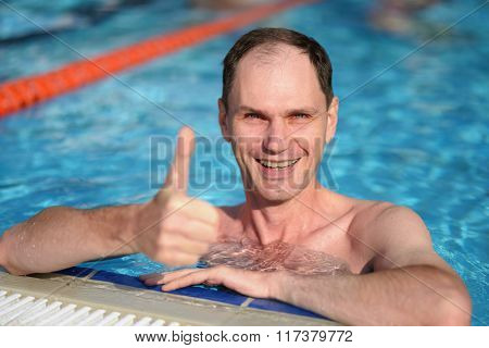 Happy man giving the thumbs up sign in a swimming pool