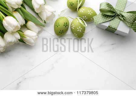 Easter eggs,tulips and gift box on white marble