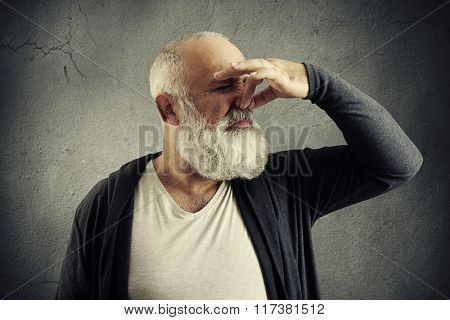 bearded man closed his nose and pulling face over dark background