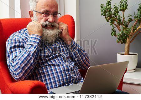 angry senior man looking at laptop and tearing his beard at home