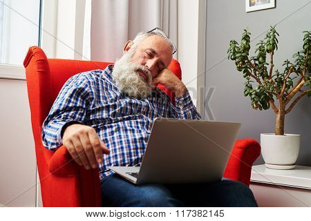 tired senior man sleeping with laptop on the chair at home