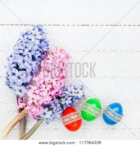 Easter Eggs And Hyacinths On White Tablecloth. Top View, Copy Space