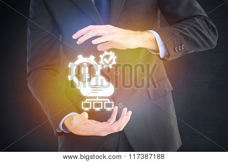 Mid section of a businessman presenting with his hands against black room