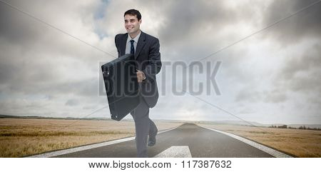 Smiling businessman in a hurry against green road landscape