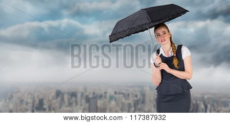 Pretty redhead businesswoman holding umbrella against clouds over city