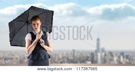 Pretty redhead businesswoman holding umbrella against balcony overlooking city