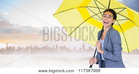 Portrait of happy businesswoman holding umbrella against dusty path in desert leading to city