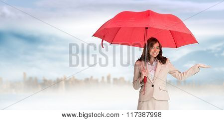 Happy businesswoman holding umbrella against large city on the horizon
