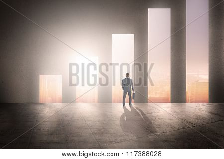 Businessman standing with his briefcase against cityscape background