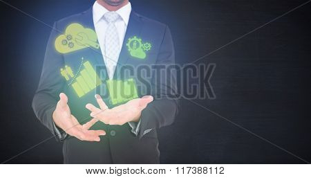 Businessman gesturing with his hands against black room