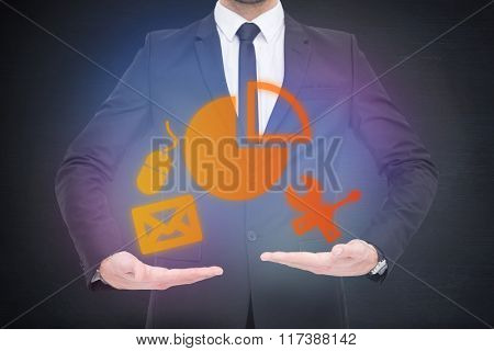 Mid section of a businessman holding something against black room