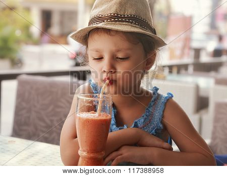 Fun Kid Girl In Hat Drinking Smoothie Juice From Glass In Street City Cafe